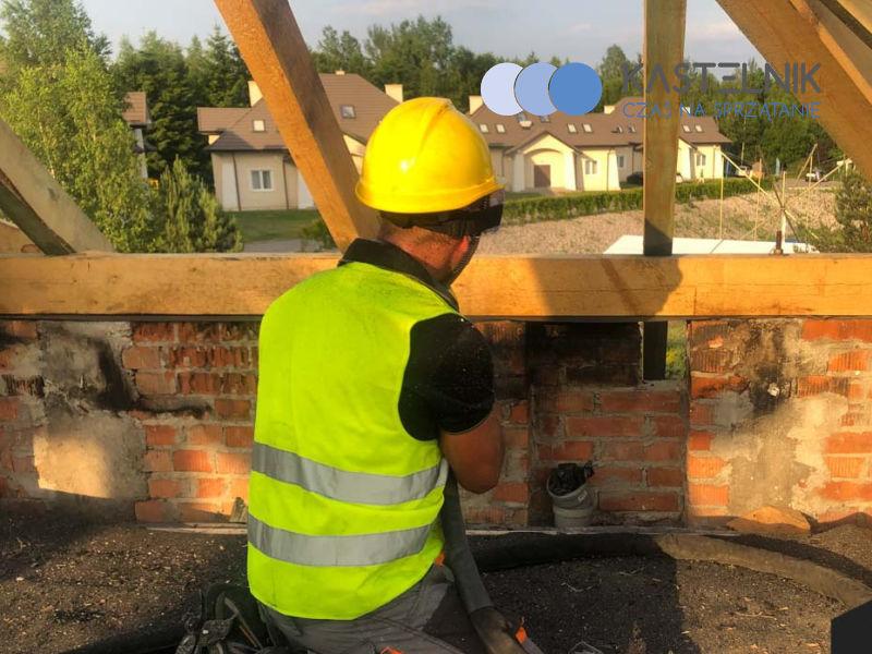 budowlaniec czyści dach po pożarze